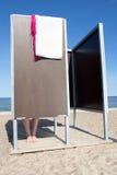 Θηλυκά πόδια στη μεταβαλλόμενη καμπίνα στην παραλία στοκ εικόνες