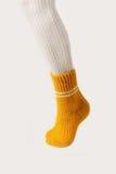 Θηλυκά πόδια στις άσπρες γυναικείες κάλτσες και τις κίτρινες πλεκτές κάλτσες Στοκ Φωτογραφίες