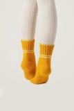 Θηλυκά πόδια στις άσπρες γυναικείες κάλτσες και τις κίτρινες πλεκτές κάλτσες Στοκ εικόνες με δικαίωμα ελεύθερης χρήσης