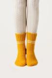 Θηλυκά πόδια στις άσπρες γυναικείες κάλτσες και τις κίτρινες πλεκτές κάλτσες Στοκ Εικόνες