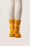 Θηλυκά πόδια στις άσπρες γυναικείες κάλτσες και τις κίτρινες πλεκτές κάλτσες Στοκ φωτογραφία με δικαίωμα ελεύθερης χρήσης