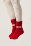 Θηλυκά πόδια στις άσπρες γυναικείες κάλτσες και τις κόκκινες πλεκτές κάλτσες Κόκκινος Στοκ εικόνες με δικαίωμα ελεύθερης χρήσης