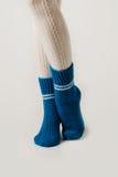 Θηλυκά πόδια στις άσπρες γυναικείες κάλτσες και τις μπλε πλεκτές κάλτσες Στοκ Εικόνα