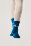 Θηλυκά πόδια στις άσπρες γυναικείες κάλτσες και τις μπλε πλεκτές κάλτσες Στοκ Φωτογραφία