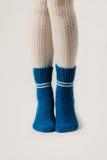 Θηλυκά πόδια στις άσπρες γυναικείες κάλτσες και τις μπλε πλεκτές κάλτσες Στοκ φωτογραφία με δικαίωμα ελεύθερης χρήσης