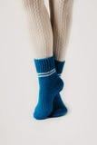 Θηλυκά πόδια στις άσπρες γυναικείες κάλτσες και τις μπλε πλεκτές κάλτσες Στοκ φωτογραφίες με δικαίωμα ελεύθερης χρήσης