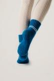Θηλυκά πόδια στις άσπρες γυναικείες κάλτσες και τις μπλε πλεκτές κάλτσες Στοκ Εικόνες