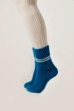 Θηλυκά πόδια στις άσπρες γυναικείες κάλτσες και τις μπλε πλεκτές κάλτσες Στοκ εικόνες με δικαίωμα ελεύθερης χρήσης