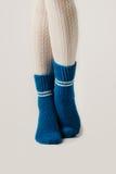 Θηλυκά πόδια στις άσπρες γυναικείες κάλτσες και τις μπλε πλεκτές κάλτσες Στοκ εικόνα με δικαίωμα ελεύθερης χρήσης