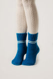 Θηλυκά πόδια στις άσπρες γυναικείες κάλτσες και τις μπλε πλεκτές κάλτσες Στοκ Φωτογραφίες