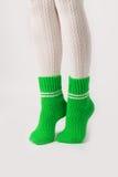 Θηλυκά πόδια στις άσπρες γυναικείες κάλτσες και τις πράσινες πλεκτές κάλτσες Στοκ φωτογραφία με δικαίωμα ελεύθερης χρήσης