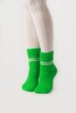 Θηλυκά πόδια στις άσπρες γυναικείες κάλτσες και τις πράσινες πλεκτές κάλτσες Στοκ Φωτογραφία