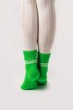 Θηλυκά πόδια στις άσπρες γυναικείες κάλτσες και τις πράσινες πλεκτές κάλτσες Στοκ φωτογραφίες με δικαίωμα ελεύθερης χρήσης