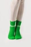 Θηλυκά πόδια στις άσπρες γυναικείες κάλτσες και τις πράσινες πλεκτές κάλτσες Στοκ Εικόνα