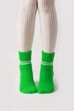 Θηλυκά πόδια στις άσπρες γυναικείες κάλτσες και τις πράσινες πλεκτές κάλτσες Στοκ Φωτογραφίες