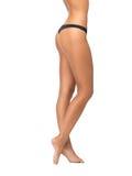 Θηλυκά πόδια στις μαύρες κιλότες μπικινιών Στοκ Εικόνες