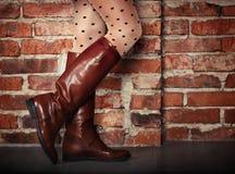 Θηλυκά πόδια στις υψηλές καφετιές μπότες δέρματος Στοκ Φωτογραφίες