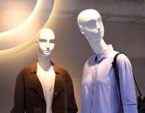 Θηλυκά πλαστικά μανεκέν πίσω από ένα παράθυρο καταστημάτων μόδας Στοκ Εικόνα