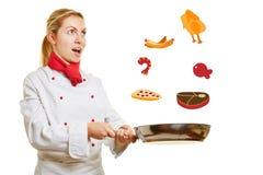 Θηλυκά τρόφιμα στροφής μαγείρων σε ένα τηγάνι Στοκ Εικόνες