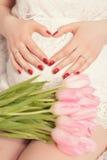 Θηλυκά χέρια Γ που διαμορφώνουν τη μορφή καρδιών στην κοιλιά έγκυος με το bouqu Στοκ εικόνες με δικαίωμα ελεύθερης χρήσης
