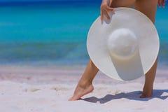 Θηλυκά χέρια και πόδια με το άσπρο καπέλο στην παραλία Στοκ Φωτογραφία