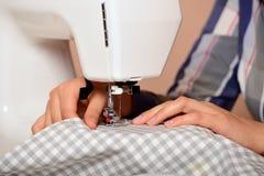 Θηλυκά χέρια κινηματογραφήσεων σε πρώτο πλάνο που ράβουν το ύφασμα στη ράβοντας μηχανή Στοκ Εικόνα