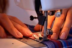 Θηλυκά χέρια κινηματογραφήσεων σε πρώτο πλάνο που ράβουν το ύφασμα στη ράβοντας μηχανή Στοκ Φωτογραφία