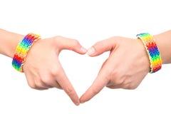 Θηλυκά χέρια με ένα βραχιόλι που διαμορφώνεται ως σημαία ουράνιων τόξων που παρουσιάζει σημάδι καρδιών Στο λευκό Στοκ εικόνα με δικαίωμα ελεύθερης χρήσης