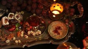 Θηλυκά χέρια με τα ασιατικά κοσμήματα που κατασκευάζουν το τσάι στο φλυτζάνι μαροκινά γλυκά παραδοσιακά Φλυτζάνι του τσαγιού γάλα φιλμ μικρού μήκους