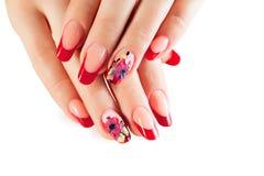 Θηλυκά χέρια με τα κόκκινα καρφιά και το σχέδιο τέχνης λουλουδιών Στοκ Εικόνες