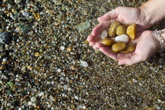 Θηλυκά χέρια με τις πέτρες θάλασσας Στοκ Φωτογραφίες