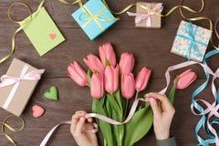 Θηλυκά χέρια με τις τουλίπες και κιβώτιο δώρων στο ξύλο Στοκ Φωτογραφίες