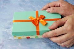 Θηλυκά χέρια που δίνουν τυλιγμένα Χριστούγεννα ή άλλες διακοπές χειροποίητο δώρο με την πορτοκαλιά κορδέλλα Στοκ Φωτογραφίες