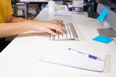 Θηλυκά χέρια που δακτυλογραφούν σε ένα πληκτρολόγιο στο γραφείο Στοκ εικόνες με δικαίωμα ελεύθερης χρήσης