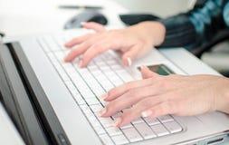 Θηλυκά χέρια που δακτυλογραφούν σε ένα πληκτρολόγιο φορητών προσωπικών υπολογιστών Στοκ φωτογραφία με δικαίωμα ελεύθερης χρήσης