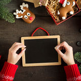 Θηλυκά χέρια που γράφουν τη λίστα επιθυμητών στόχων κοντά στα δώρα Χριστουγέννων Εορταστική κάρτα Χριστουγέννων με τον πίνακα κιμ Στοκ Φωτογραφία