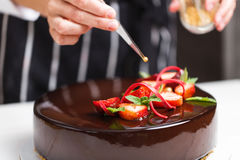 Θηλυκά χέρια που διακοσμούν το κέικ στοκ εικόνες