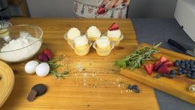 Θηλυκά χέρια που διακοσμούν muffins σοκολάτας με τη φράουλα φιλμ μικρού μήκους