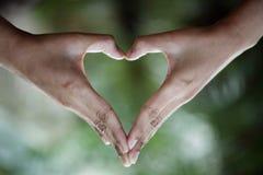 Θηλυκά χέρια που κάνουν τη μορφή καρδιών Στοκ Εικόνες