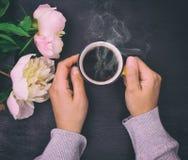 Θηλυκά χέρια που κρατούν ένα κίτρινο φλυτζάνι με το μαύρο καφέ Στοκ Φωτογραφία