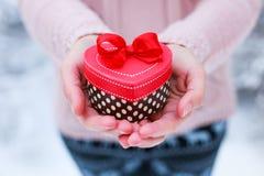 Θηλυκά χέρια που κρατούν ένα κιβώτιο δώρων Στοκ Εικόνες