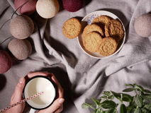 Θηλυκά χέρια που κρατούν ένα φλυτζάνι του γάλακτος Στα κέικ υποβάθρου Στοκ Εικόνα