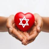 Θηλυκά χέρια που κρατούν την καρδιά με το αστέρι του Δαυίδ Στοκ φωτογραφία με δικαίωμα ελεύθερης χρήσης