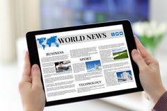 Θηλυκά χέρια που κρατούν την ταμπλέτα με app τις παγκόσμιες ειδήσεις στην οθόνη Στοκ Εικόνες