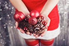 Θηλυκά χέρια που κρατούν τις κόκκινους διακοσμήσεις Χριστουγέννων και τους κώνους, λαμπρό υπόβαθρο Χριστουγέννων Δώρο και διακοσμ Στοκ Εικόνες