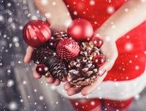Θηλυκά χέρια που κρατούν τις κόκκινους διακοσμήσεις Χριστουγέννων και τους κώνους, λαμπρό υπόβαθρο Χριστουγέννων Δώρο και διακοσμ Στοκ φωτογραφίες με δικαίωμα ελεύθερης χρήσης