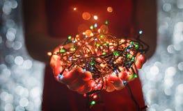 Θηλυκά χέρια που κρατούν τις πολύχρωμες ελαφριές διακοσμήσεις Χριστουγέννων στο σκοτεινό υπόβαθρο διακοπών Χριστούγεννα και νέο θ Στοκ Εικόνες