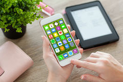 Θηλυκά χέρια που κρατούν το άσπρο τηλέφωνο με τα εικονίδια εγχώριας οθόνης apps Στοκ Εικόνες