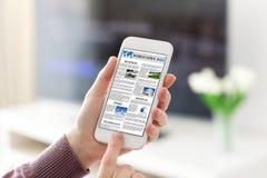 Θηλυκά χέρια που κρατούν το τηλέφωνο με app τις παγκόσμιες ειδήσεις στην οθόνη Στοκ εικόνες με δικαίωμα ελεύθερης χρήσης