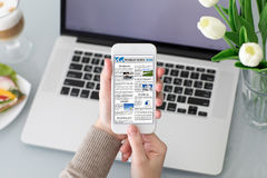 Θηλυκά χέρια που κρατούν το τηλέφωνο με app τις παγκόσμιες ειδήσεις στην οθόνη Στοκ Φωτογραφίες